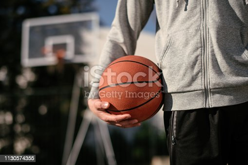 Man holds the ball for basketball. Shallow DOF. Developed from RAW; retouched with special care and attention; Small amount of grain added for best final impression. 16 bit Adobe RGB color profile.