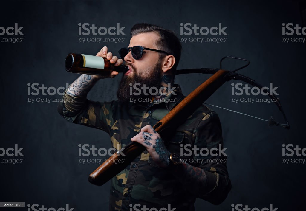 A man holds the craft beer bottle and a crossbow. stock photo