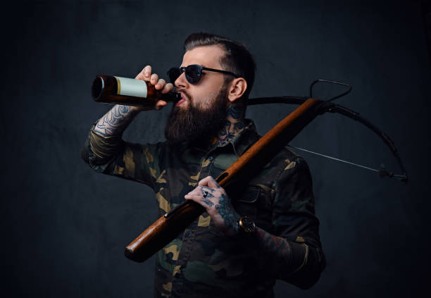 a man holds the craft beer bottle and a crossbow. - crossbow stock pictures, royalty-free photos & images