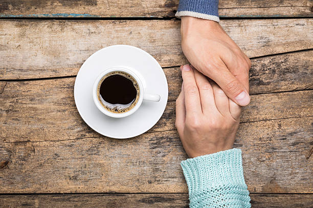 Man holds woman's hand with cup of coffee Man holds woman's hand with cup of coffee top view image on wooden backdrop. Friendship coffee background sergionicr stock pictures, royalty-free photos & images