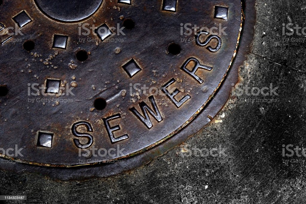 Man hole cover for sewer entry with iron grate on street in a city Man hole cover for sewer entry with iron grate on street in a city Abstract Stock Photo