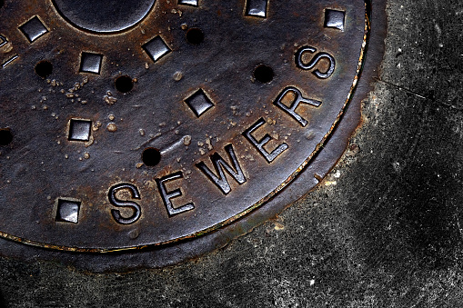 Man Hole Cover For Sewer Entry With Iron Grate On Street In A City Stock Photo - Download Image Now