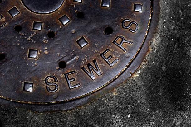 mann hole deckung für kanaleintrag mit eisengitter auf der straße in einer stadt - kanalisationsabflüsse stock-fotos und bilder
