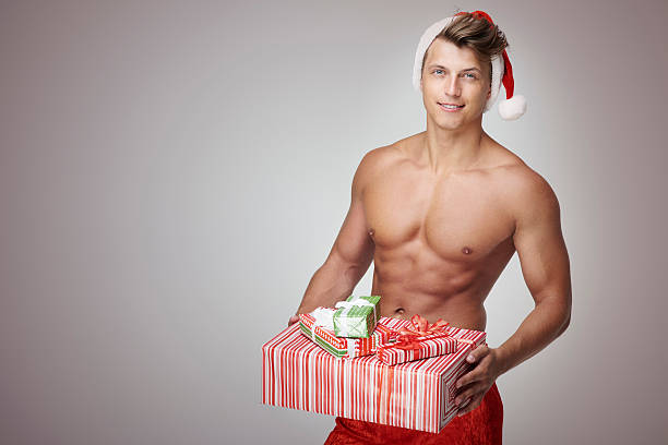 man holidng stack of christmas presents - naked santa claus stock pictures, royalty-free photos & images