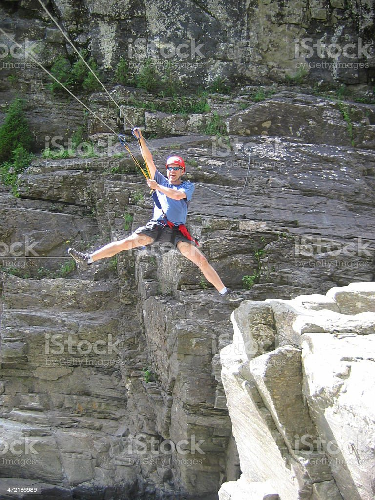 man hooked on cable with harness crossing with tyrolean stock photo