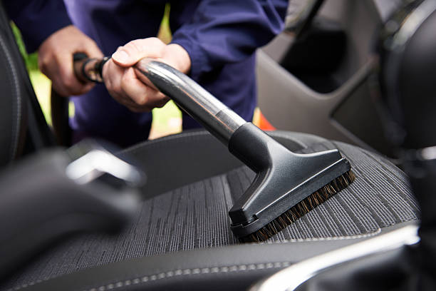 man hoovering seat of car during car cleaning - car interior stock photos and pictures
