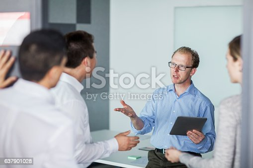 637940820 istock photo Man hosting business meeting in office 637901028