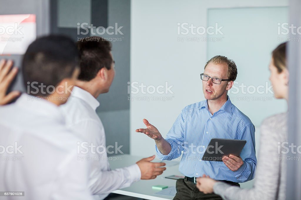 Man hosting business meeting in office stock photo