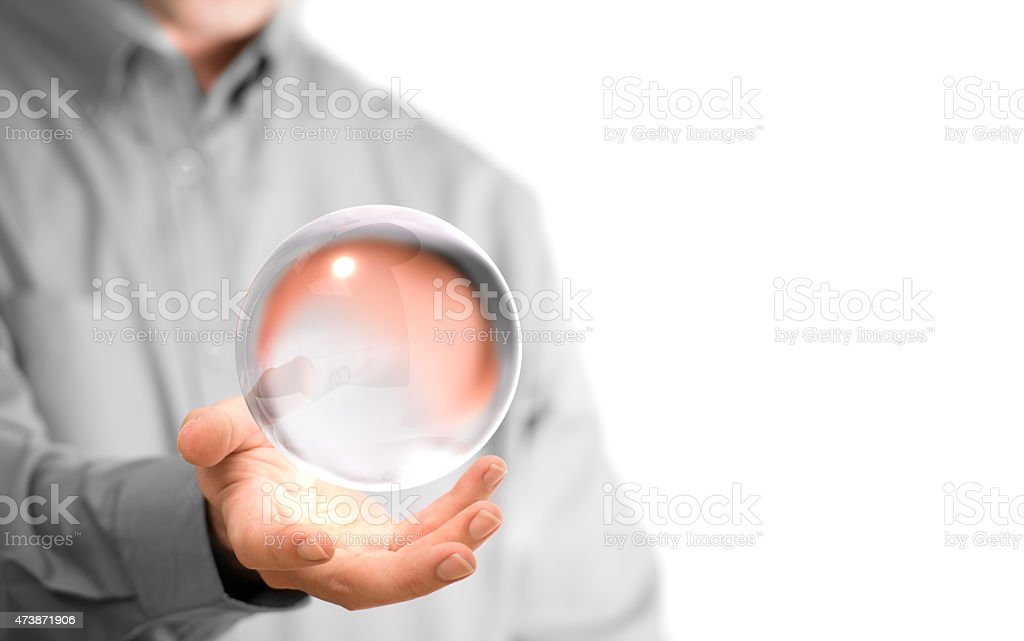 Man hovering a clear crystal ball above his hands stock photo