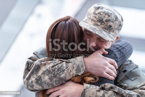 A handsome man dressed in a military uniform passionately hugs his partner as he greets her returning from his military service in this close-up.