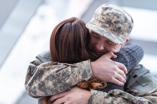 Man hugging his wife after returning home from service A handsome man dressed in a military uniform passionately hugs his partner as he greets her returning from his military service in this close-up. husband stock pictures, royalty-free photos & images