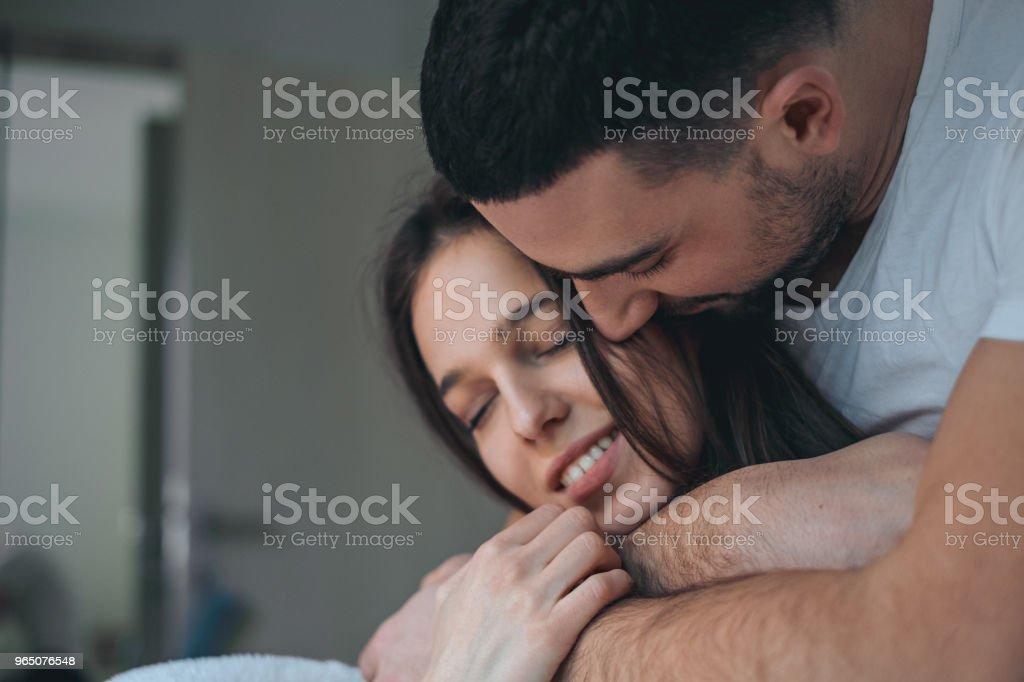 Man hugging smiling girlfriend with closed eyes zbiór zdjęć royalty-free