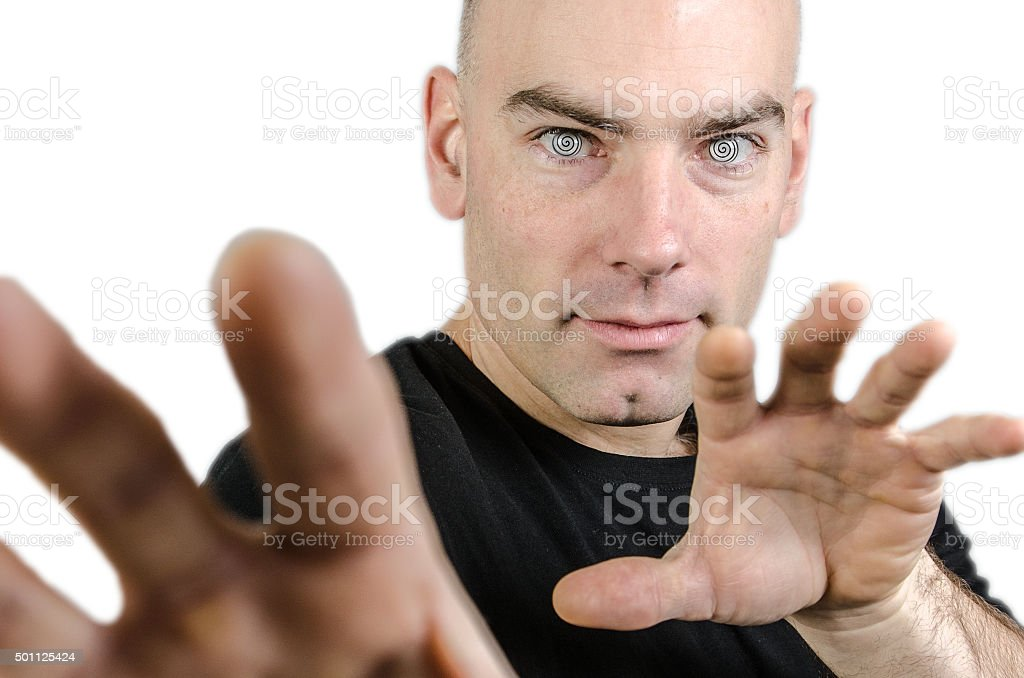 Man hypnotist with hands in front of camera, studio shot, stock photo