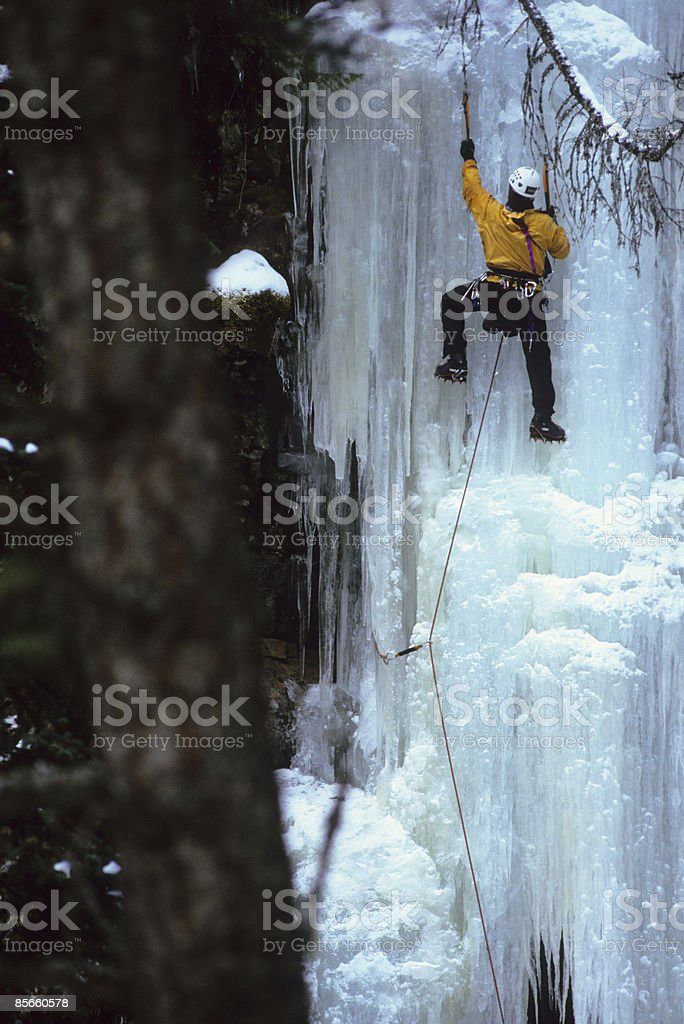 Man ice climbing frozen waterfall. photo libre de droits