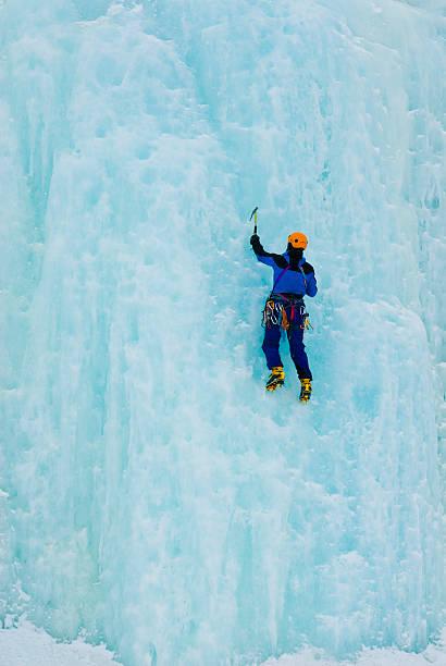 man iceclimbing た凍った滝 - アイスクライミング ストックフォトと画像