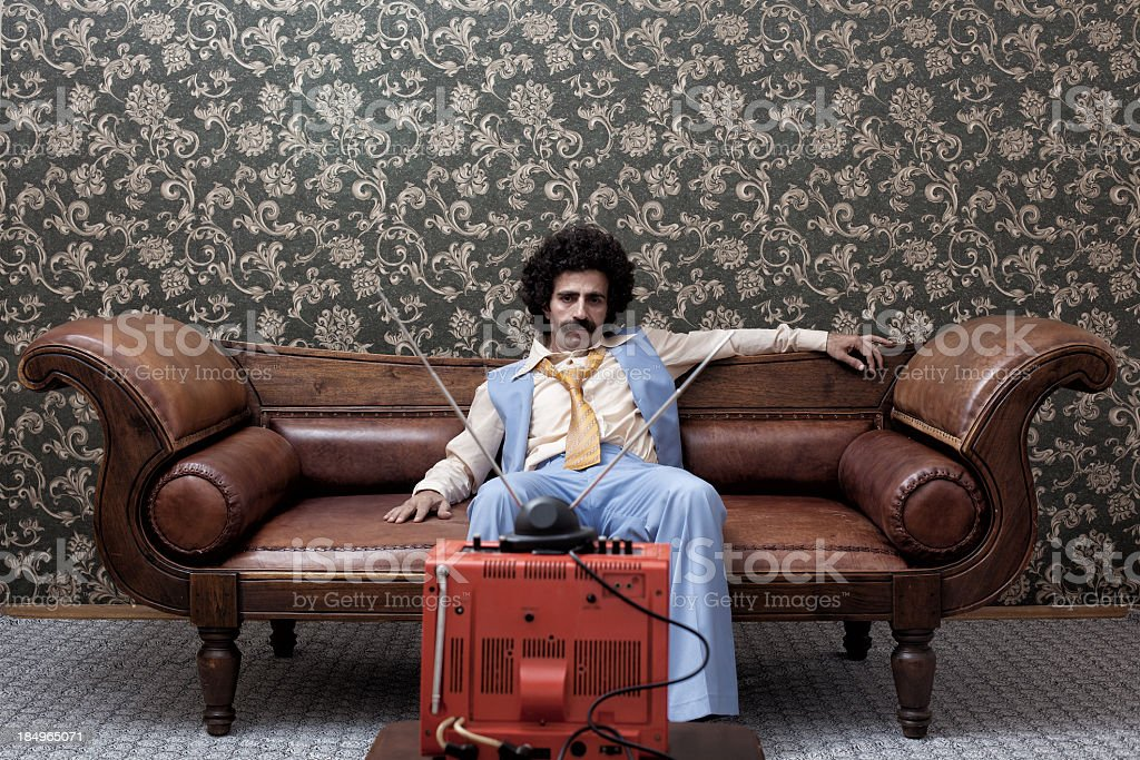 Man In 1970s Style Sitting On Sofa Watching Television stock photo