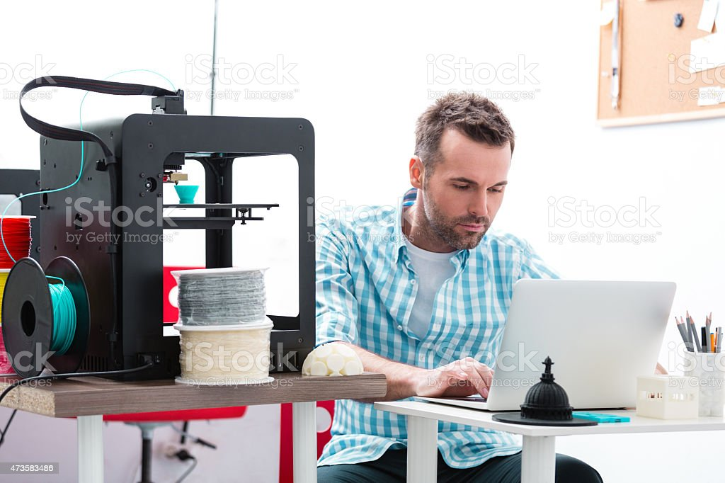 Man in 3D printer office using laptop Man working in a 3d printer office, sitting at the table and using laptop. 2015 Stock Photo