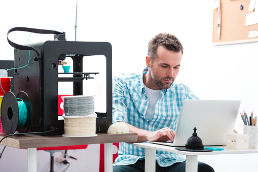 Man In 3d Printer Office Using Laptop Stock Photo - Download Image Now