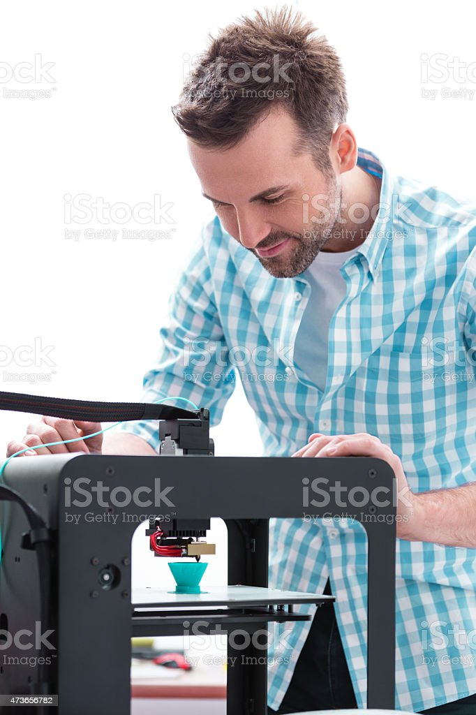 Man in 3D printer office watching printing Close up of an attractive man working in a 3D printer office and watching 3D printing.  2015 Stock Photo