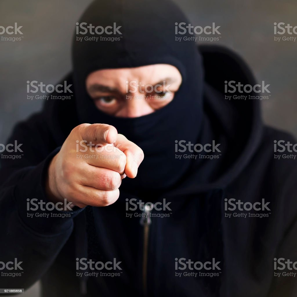 A man in a balaclava on a dark background. Copy space. Concept stealing, deception stock photo