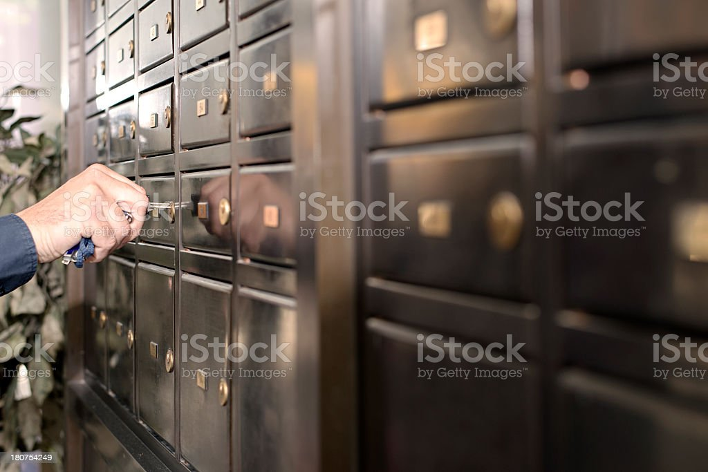 Man in a bank opening a safety deposit box stock photo