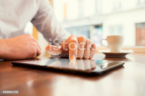 istock Man in a bar using tablet pc. Window background. 493694230