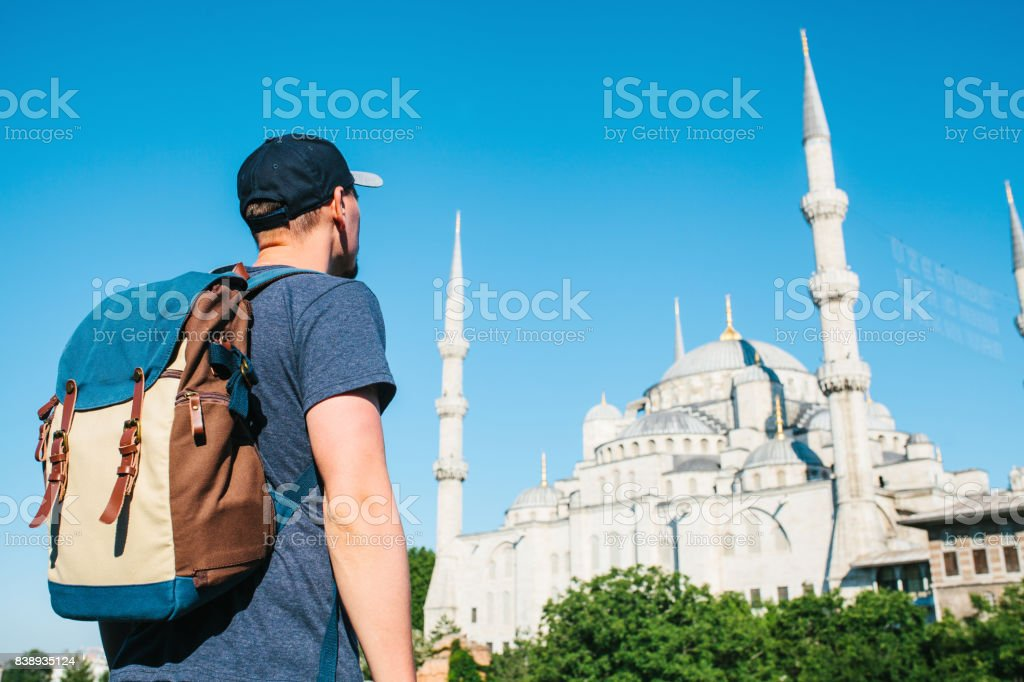 A man in a baseball cap with a backpack next to the blue mosque is a famous sight in Istanbul. Travel, tourism, sightseeing. stock photo