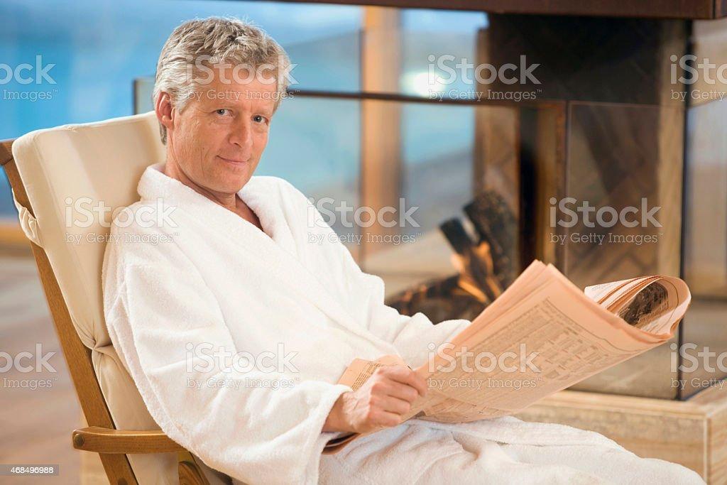 Hombre en una bata de baño, sala de estar, periódico sonriente retención en sillas de playa - foto de stock