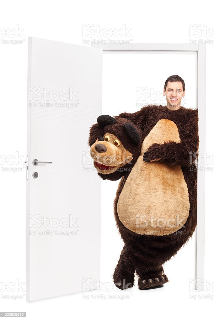 Man in a bear costume leaning on a door stock photo