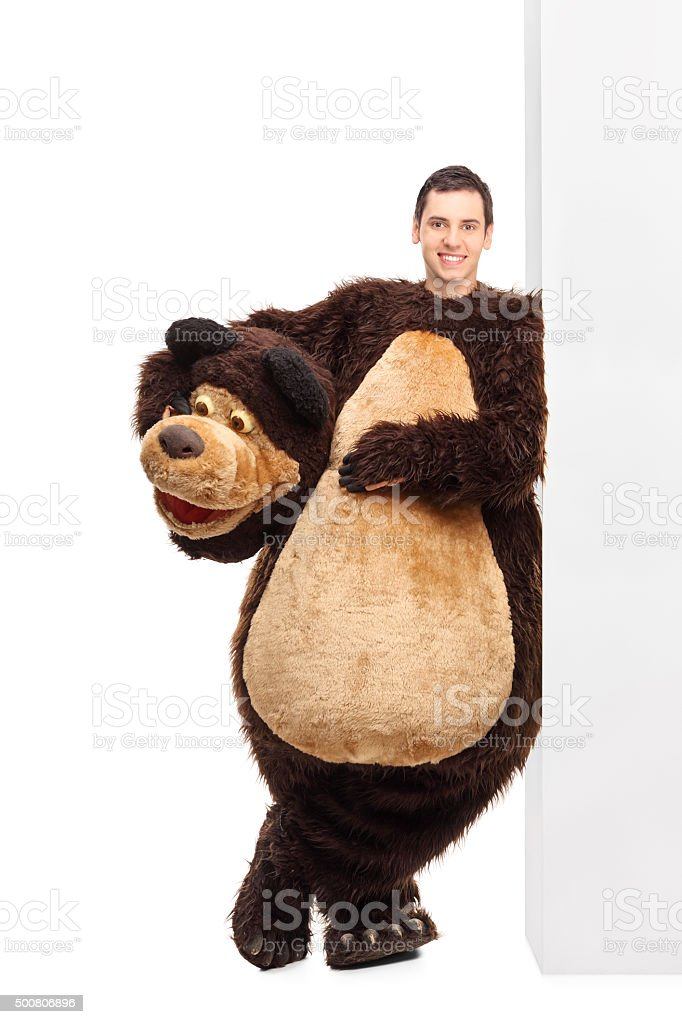 Man in a bear costume leaning on a wall stock photo