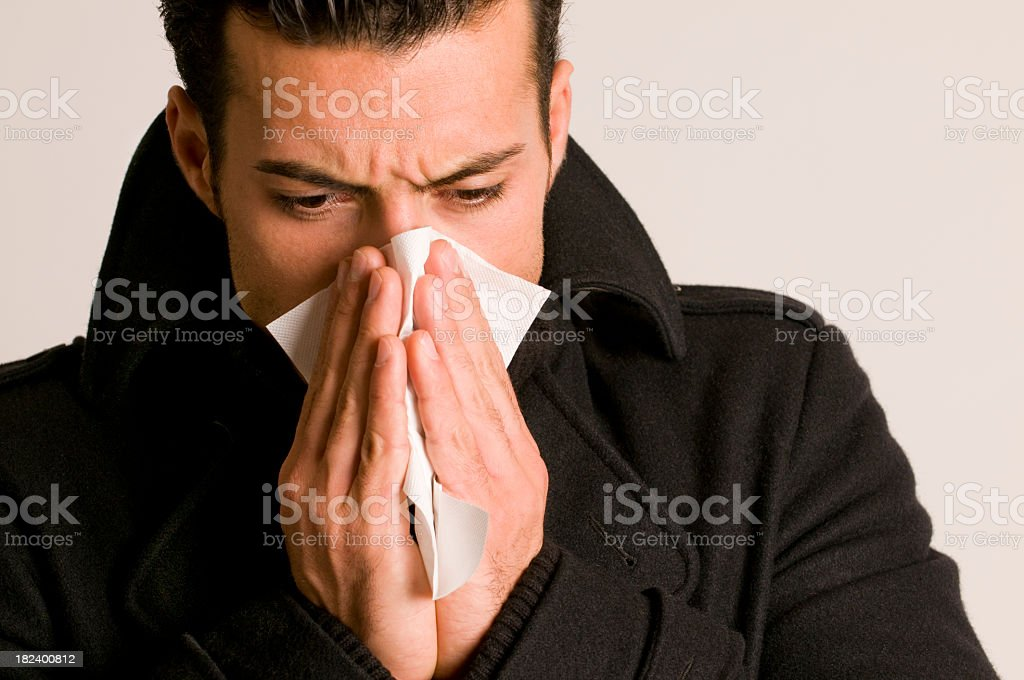 Man in a black coat blowing his nose in a napkin stock photo