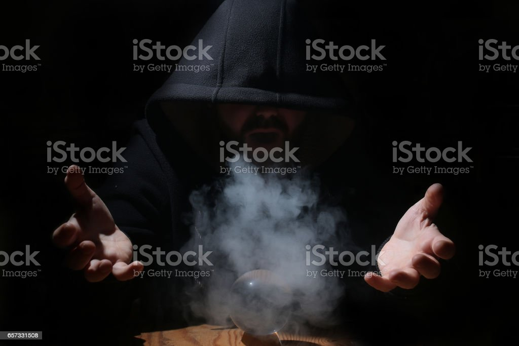 man in a black hood with cristal ball stock photo