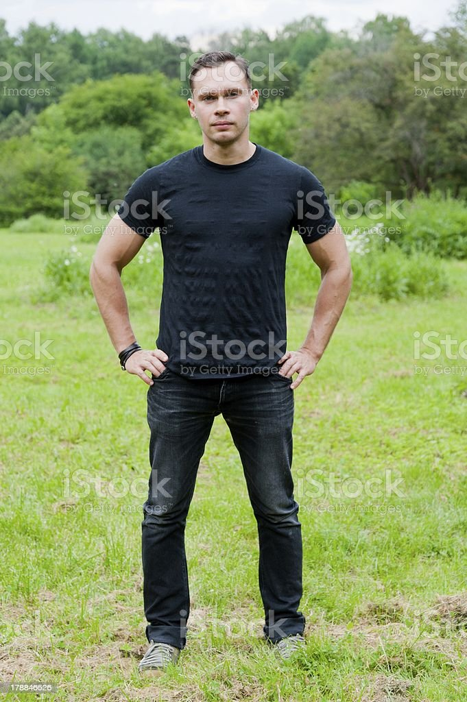 Man in a black t-shirt stands on the grass royalty-free stock photo