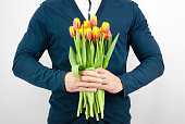 Man in a blue jacket holding a bouquet of tulips