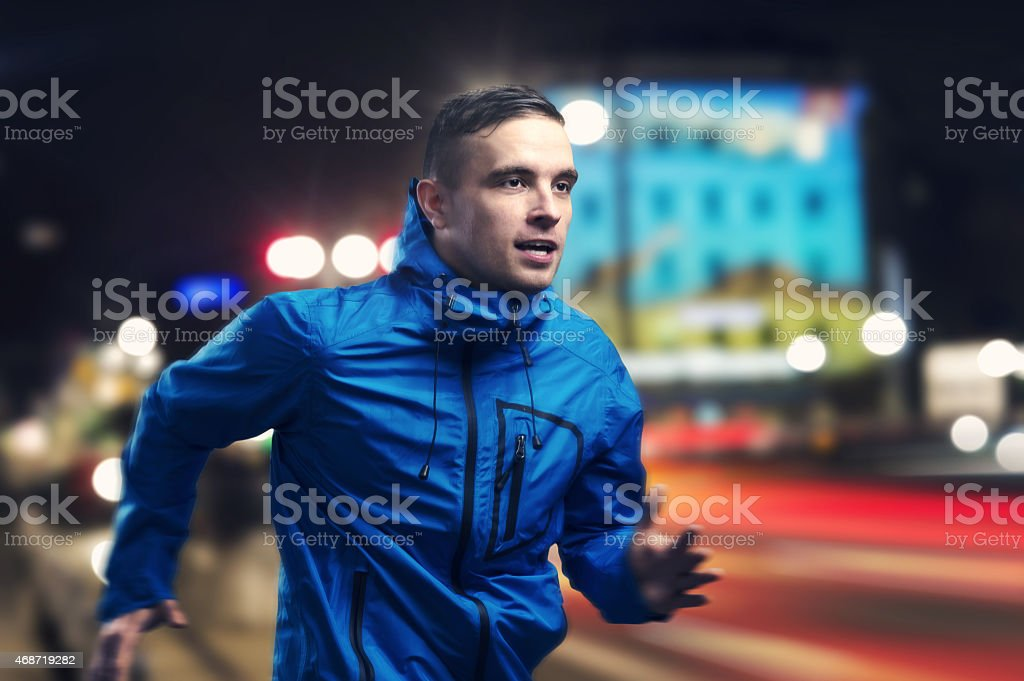 A man in a blue jacket running in the evening stock photo