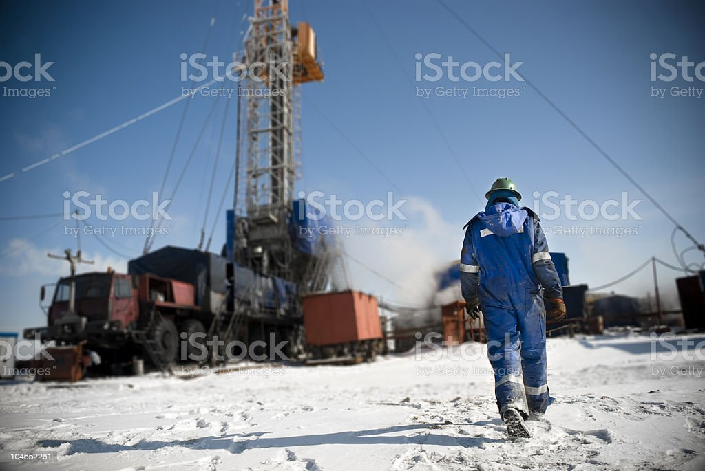 Man in a blue jumpsuit walking onto snowy construction site stock photo