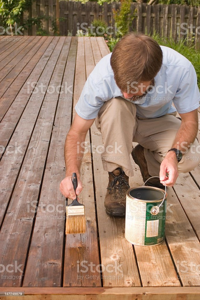 A man in a blue polo repainting his wood decking stock photo