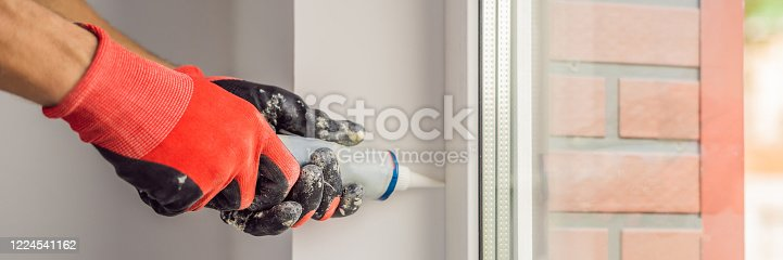 1070686034 istock photo Man in a blue shirt does window installation BANNER, LONG FORMAT 1224541162