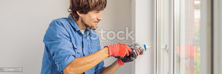 945456460 istock photo Man in a blue shirt does window installation BANNER, LONG FORMAT 1224541172
