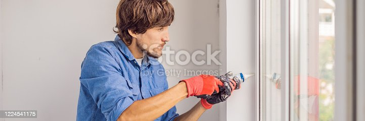 945456460 istock photo Man in a blue shirt does window installation BANNER, LONG FORMAT 1224541175