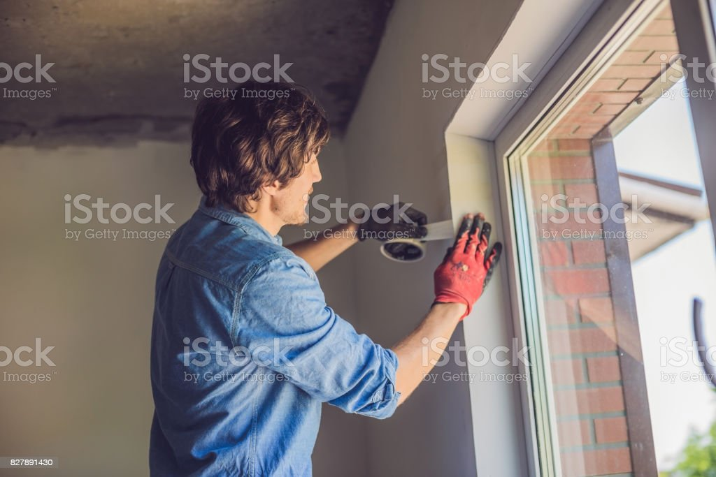Man in a blue shirt does window installation stock photo