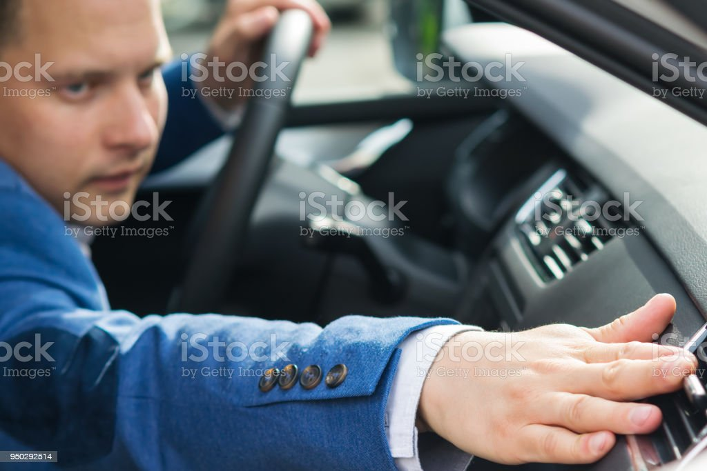 man in a blue suit adjusts the air intake in the car stock photo