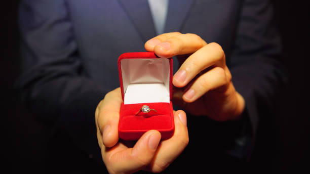 man in a blue suit gives a ring with a diamond in a red box - diamond ring hand stock photos and pictures