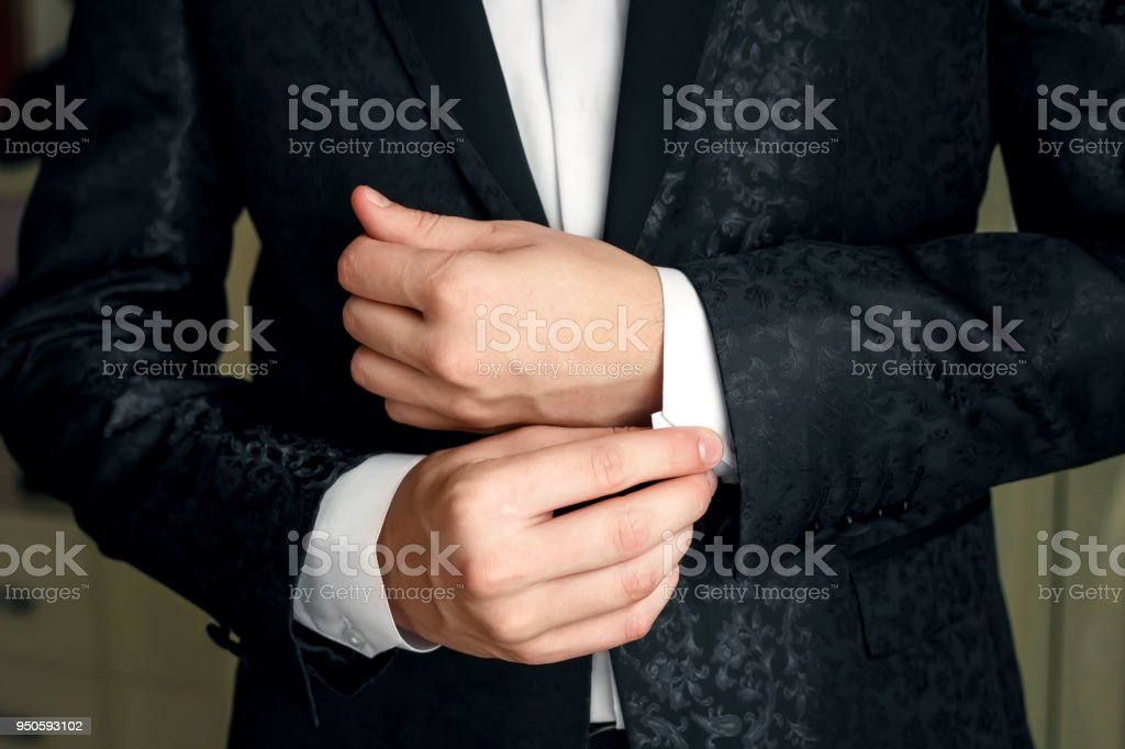 A man in a blue suit straightens his sleeves stock photo