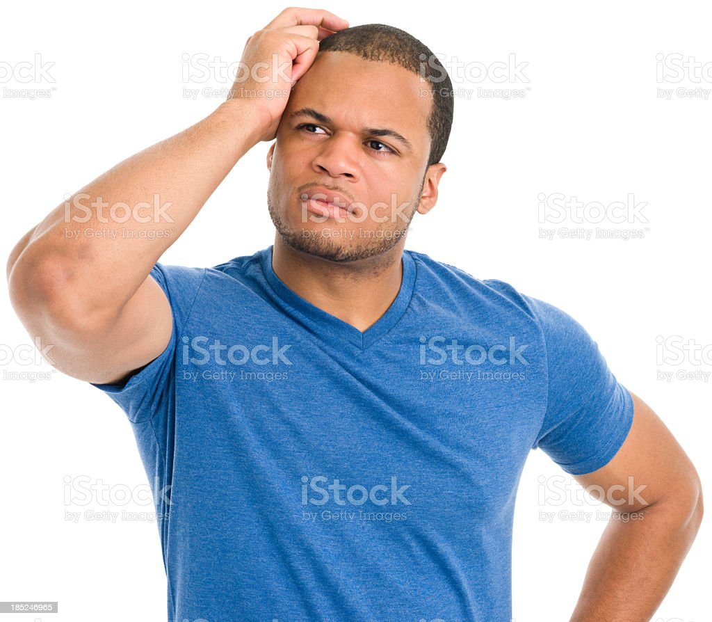 Man in a blue tee scratching his head while thinking stock photo