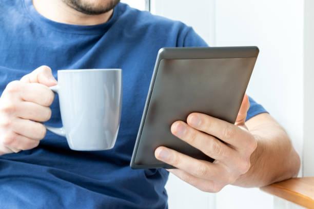 Un homme dans un t-shirt bleu tient un livre électronique gris d'e-reader dans une main et une tasse dans l'autre. Lecture d'un livre ou de nouvelles sur une tablette au petit déjeuner. Mise au point sélective - Photo