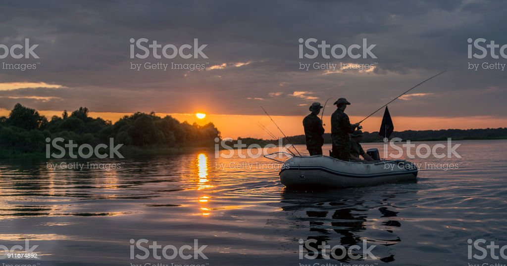 Man in a boat at sunset fish. stock photo