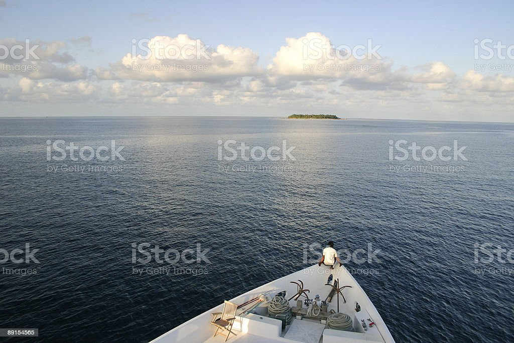 man in a boat heading to remote uninhibited island royalty-free stock photo