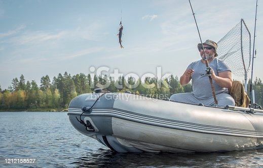 1030273092 istock photo A man in a boat with a spinning rod and caught fish. 1212158527