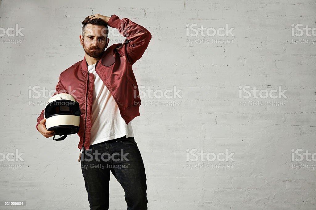 Man in a bordeaux pilot jacket with helmet stock photo